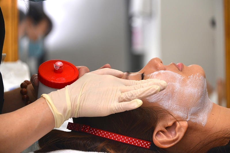 Numbing cream is applied to Ju Ann's face to ease the feeling of discomfort during the procedure.
