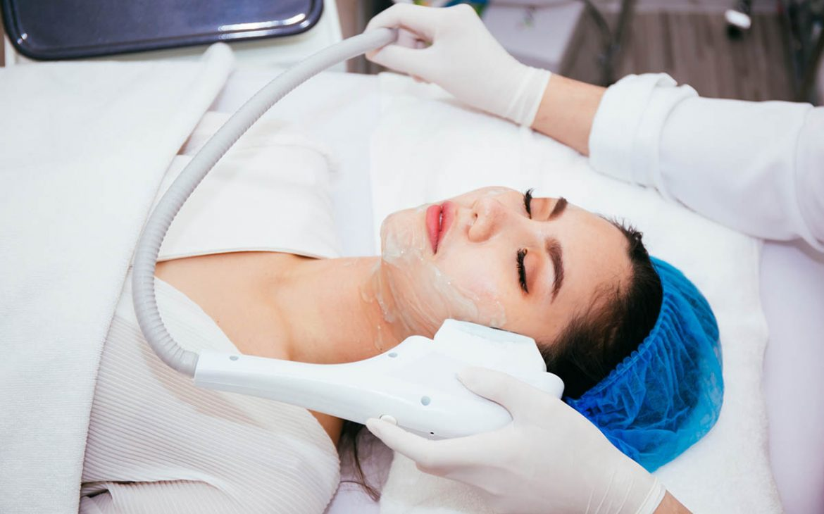 Young Asian woman getting facial skin treatment by beautician at beauty clinic.