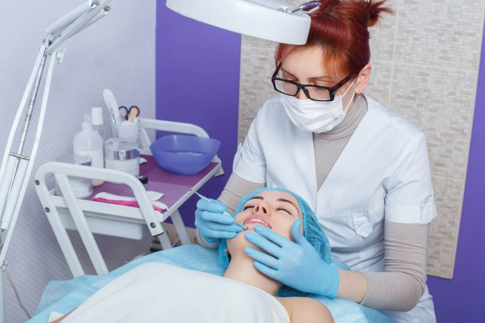doctor treating acne on patient